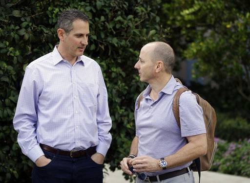 Thad Levine, left, general manager for the Minnesota Twins and New York Yankees general manager Brian Cashman, right, talk at the annual MLB baseball general managers' meetings, Tuesday, Nov. 14, 2017, in Orlando, Fla.