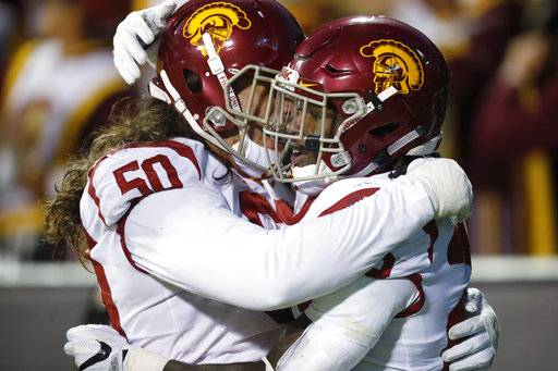 USC guard Toa Lobendahn, left, congratulates running back Ronald Jones II after his touchdown run against Colorado in the second half of an NCAA college football game Saturday, Nov. 11, 2017, in Boulder, Colo. USC won 38-24.