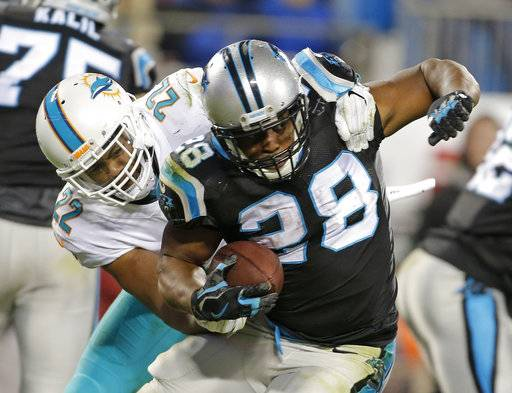 Carolina Panthers' Jonathan Stewart (28) is tackled by Miami Dolphins' T.J. McDonald (22) in the second half of an NFL football game in Charlotte, N.C., Monday, Nov. 13, 2017.