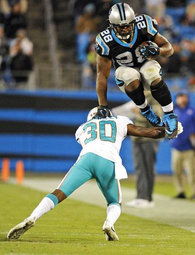 Carolina Panthers' Jonathan Stewart (28) leaps over Miami Dolphins' Cordrea Tankersley (30) in the second half of an NFL football game in Charlotte, N.C., Monday, Nov. 13, 2017.