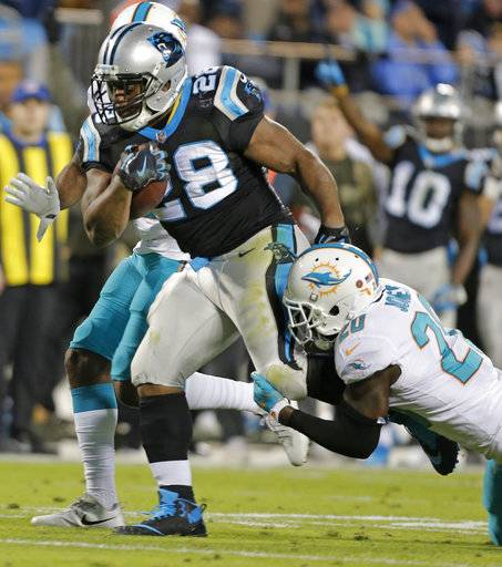 Carolina Panthers' Jonathan Stewart (28) runs as Miami Dolphins' Reshad Jones (20) defends in the first half of an NFL football game in Charlotte, N.C., Monday, Nov. 13, 2017.