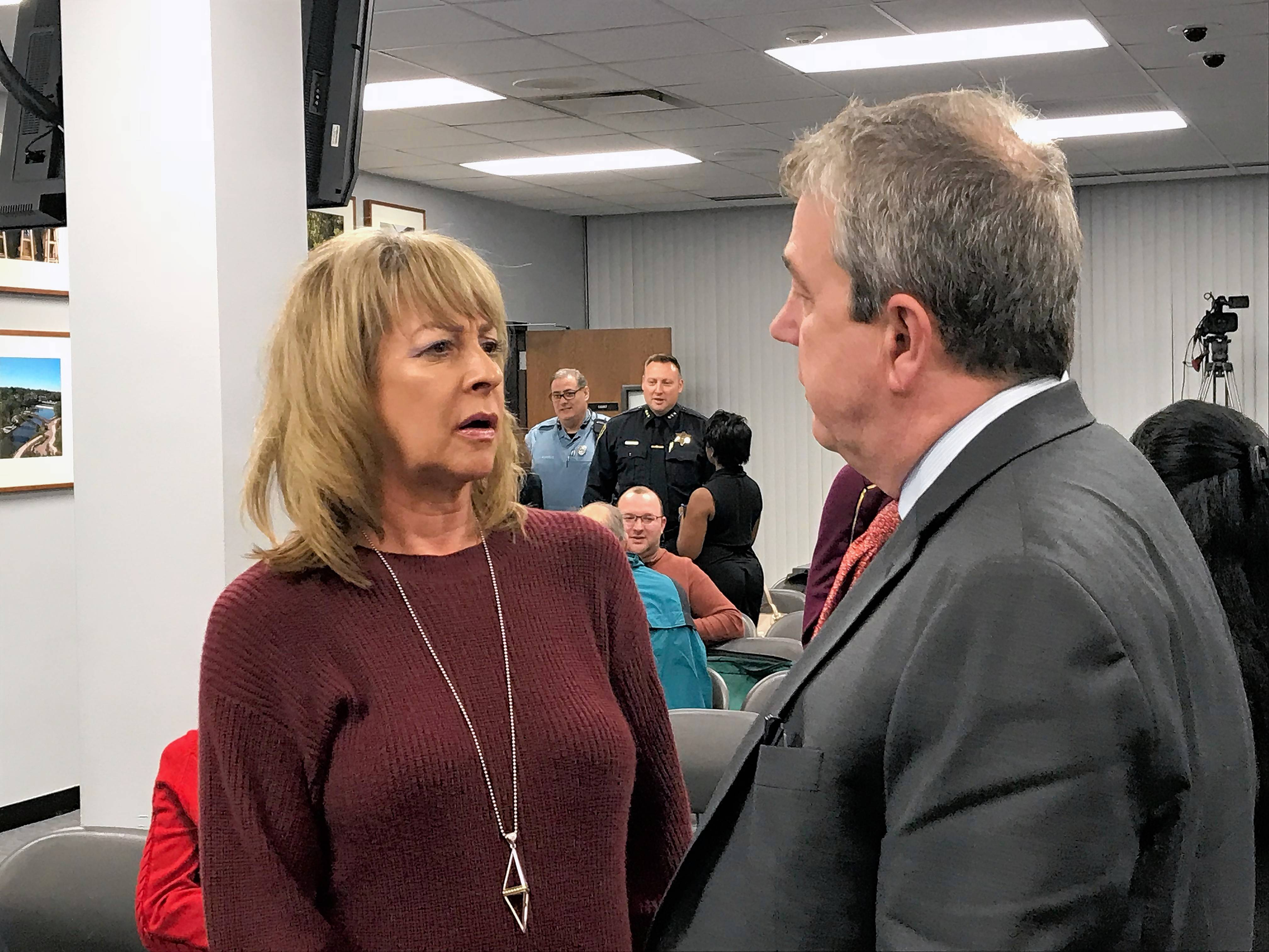 Kim Bless, left, president and CEO of the Elgin Area Convention and Visitors Bureau, talks to a supporter Wednesday before the Elgin City Council meeting.