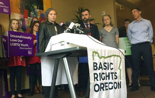 Elliot Yoder, 16, a transgender student at Dallas High School in Dallas, Ore., speaks at a news conference held by ACLU Oregon and Basic Rights in Portland, Ore., Thursday, Nov. 16, 2017, to protest a federal lawsuit filed against the Dallas School District over its policy on the treatment of transgender students. The district began allowing Yoder to use the boys' locker room and boys' restrooms after he publicly identified as transgender. (AP Photo/Gillian Flaccus)
