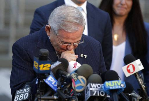 U.S. Sen. Bob Menendez fights tears as he speaks to reporters outside Martin Luther King Jr. Federal Courthouse after U.S. District Judge William Walls declared a mistrial in Menendez's federal corruption trial, Thursday, Nov. 16, 2017, in Newark, N.J. (AP Photo/Julio Cortez)