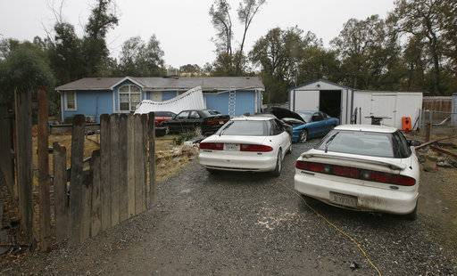Cars are parked in front of the home of Kevin Janson Neal Wednesday, Nov. 15, 2017, in Rancho Tehama Reserve, Calif. The body of Neal's wife was found at the home, where Neal started his shooting rampage that left four others dead, before he was shot and killed by Tehama County Sheriff's deputies. (AP Photo/Rich Pedroncelli)