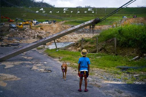 FILE - In this Oct. 17, 2017 file photo, a boy accompanied by his dog watches the repairs of Guajataca Dam, which cracked during the passage of Hurricane Maria, in Quebradillas, Puerto Rico. Experts said on Thursday, Nov. 16, 2017, that Puerto Rico could face nearly two decades of further economic stagnation and a steep drop in population as a result of Maria. (AP Photo/Ramon Espinosa, File)