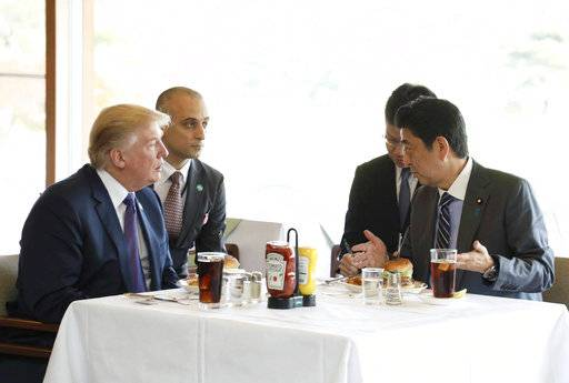 FILE - In this Nov. 5, 2017, file photo from the Prime Minister's Office Facebook page, U.S. President Donald Trump, left, listens to Japanese Prime Minister Shinzo Abe, right, during a lunch of hamburgers from Munch's Burger Shack at Kasumigaseki Country Club in Kawagoe, Japan. The cheeseburger Trump had is still drawing lines to the Tokyo burger joint. (Cabinet Public Relations Office of Japan via AP)