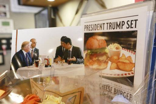 A photo showing U.S. President Donald Trump, left, and Japanese Prime Minister Shinzo Abe, right, at a lunch of hamburgers from Munch's Burger Shack at Kasumigaseki Country Club, is displayed at the burger restaurant in Tokyo Thursday, Nov. 16, 2017. The cheeseburger Trump had is still drawing lines at the Tokyo burger joint.
