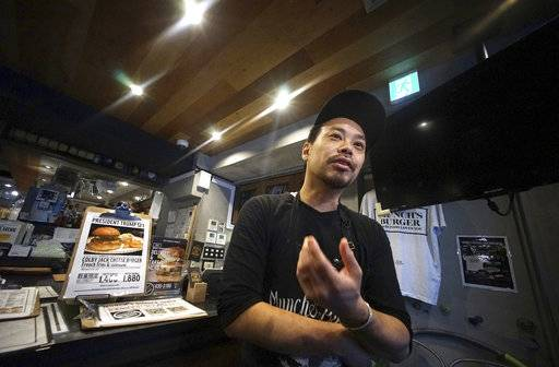 Yutaka Yanagisawa, owner of Munch's Burger Shack restaurant, speaks during an interview with The Associated Press in Tokyo Thursday, Nov. 16, 2017. The cheeseburger U.S. President Donald Trump had during his recent visit to Japan is still drawing lines at the Tokyo burger joint.
