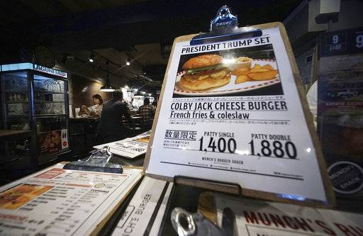 A menu showing U.S. President Donald Trump set is seen at Munch's Burger Shack restaurant in Tokyo Thursday, Nov. 16, 2017. The cheeseburger Trump had during his recent visit to Japan is still drawing lines at the Tokyo burger joint.