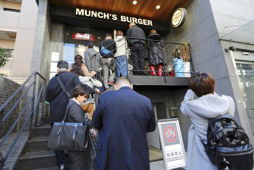 A line of customers queue up to have their lunch at Munch's Burger Shack restaurant in Tokyo Thursday, Nov. 16, 2017. The cheeseburger U.S. President Donald Trump had during his recent visit to Japan is still drawing lines at the Tokyo burger joint.