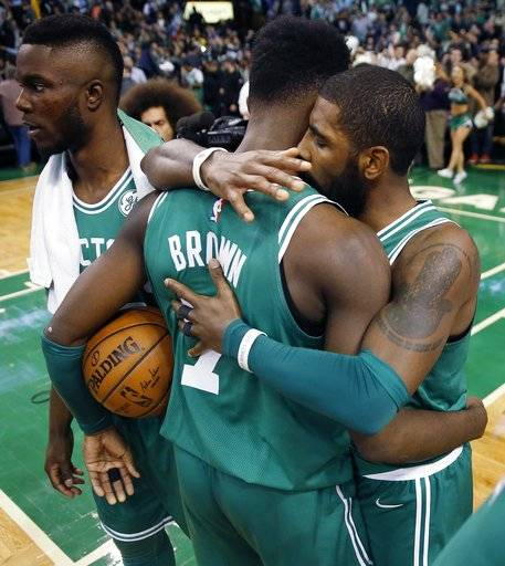 Boston Celtics' Kyrie Irving, right, hugs teammate Jaylen Brown (7) after defeating the Golden State Warriors 92-88 during an NBA basketball game in Boston, Thursday, Nov. 16, 2017. (AP Photo/Michael Dwyer)