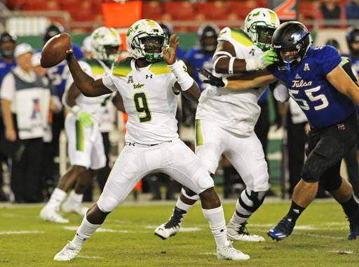 South Florida quarterback Quinton Flowers (9) passes under pressure from Tulsa's Garrett Flanary (55) during the first half of an NCAA college football game Thursday, Nov. 16, 2017, in Tampa, Fla. (AP Photo/Steve Nesius)