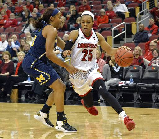 Louisville guard Asia Durr (25) drives around Michigan guard Deja Church during the second half of an NCAA college basketball game, Thursday, Nov. 16, 2017, in Louisville, Ky. (AP Photo/Timothy D. Easley)