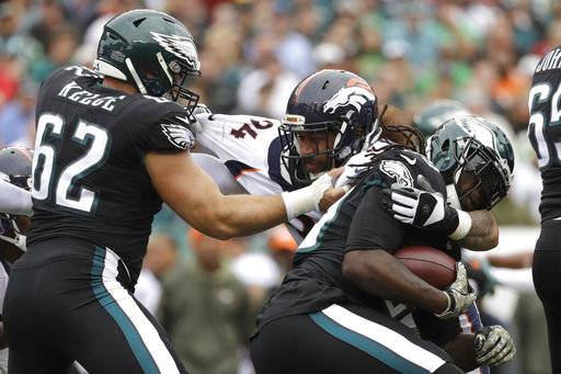 FILE - In this Nov. 5, 2017, file photo, Philadelphia Eagles' Jay Ajayi, right, tries to slip past Denver Broncos' Domata Peko, center, with help from Jason Kelce (62) during the first half of an NFL football game in Philadelphia. Peko had no idea when he left Cincinnati for Denver in free agency this spring that he was trading one sad situation for another. (AP Photo/Michael Perez,File)