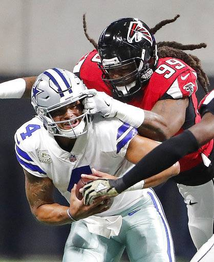 "FILE-This Nov. 12, 2017, file photo shows Atlanta Falcons defensive end Adrian Clayborn (99) sacking Dallas Cowboys quarterback Dak Prescott (4) during the first half of an NFL football game, in Atlanta. Since turning in one of the greatest pass-rushing performances in NFL history, Clayborn has doled out Thanksgiving meals to the needy, shaken hands with Jay-Z _ and gotten the brush-off from his dogs. Turns out, Ace and King were none too impressed with those six sacks. When he jumped on the floor to play with them, they ignored their owner and started jostling with each other. ""My dogs don't like me very much,� Clayborn joked Thursday, Nov. 16, 2017. (AP Photo/David Goldman, File)"