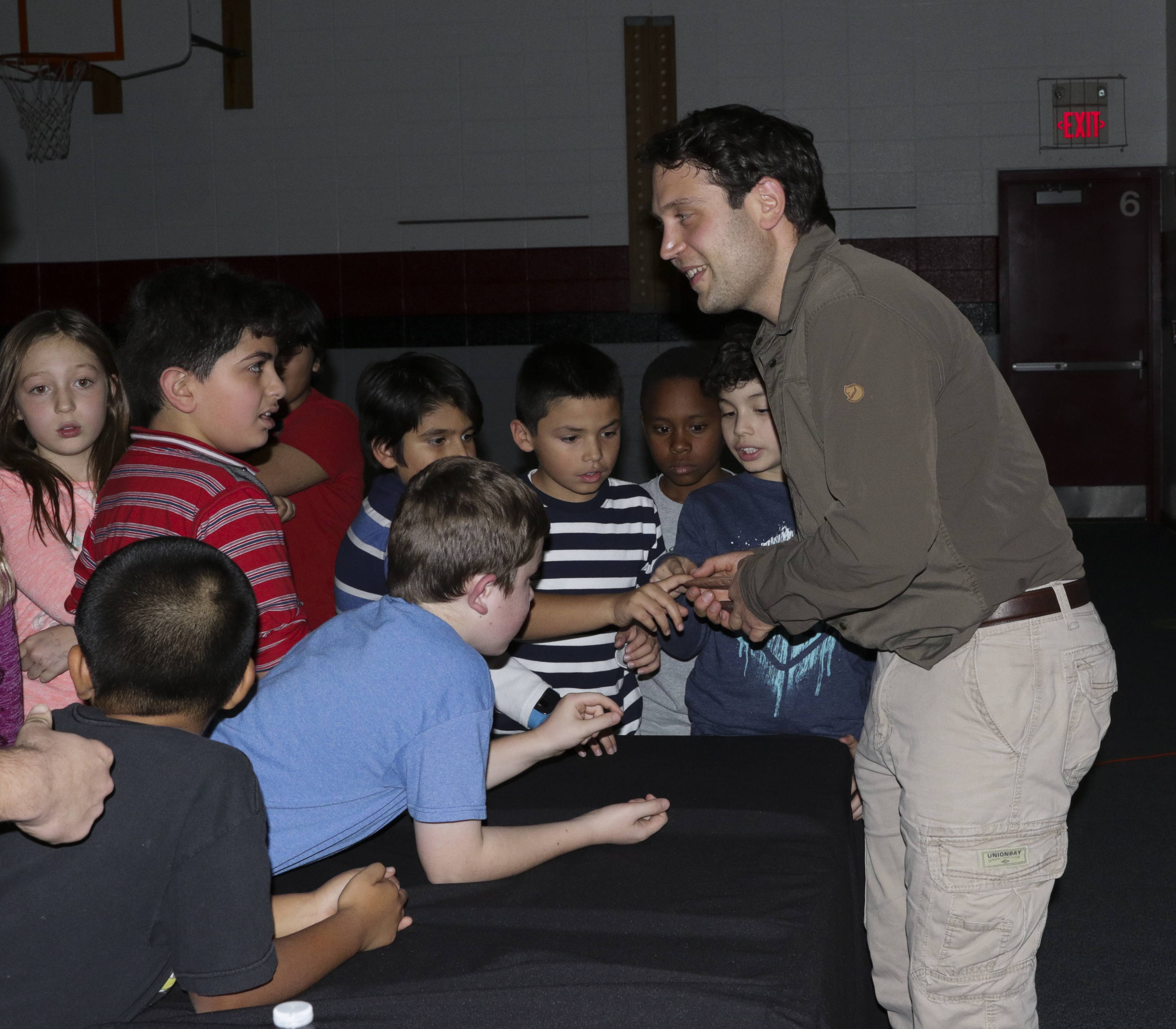 Paleontologist and National Geographic Explorer Nizar Ibrahim shows kids some dinosaur fossils at McCarty Elementary School in Aurora.