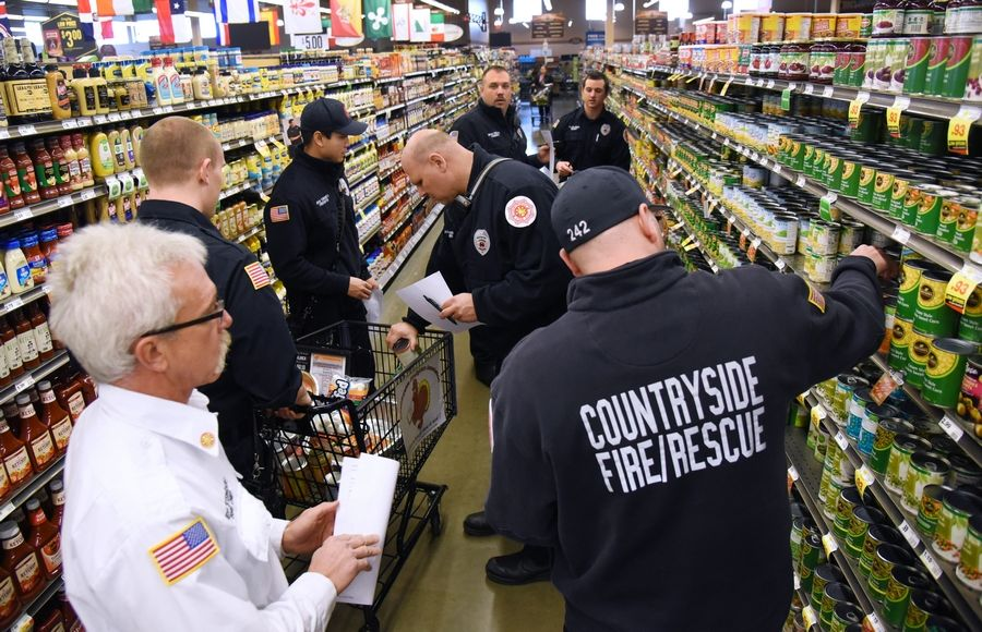 Members of the Countryside Firefighter' Association shop for groceries Friday morning at the Vernon Hills Mariano's to provide Thanksgiving dinners for area families in Libertyville, Vernon, Ela and Fremont townships.