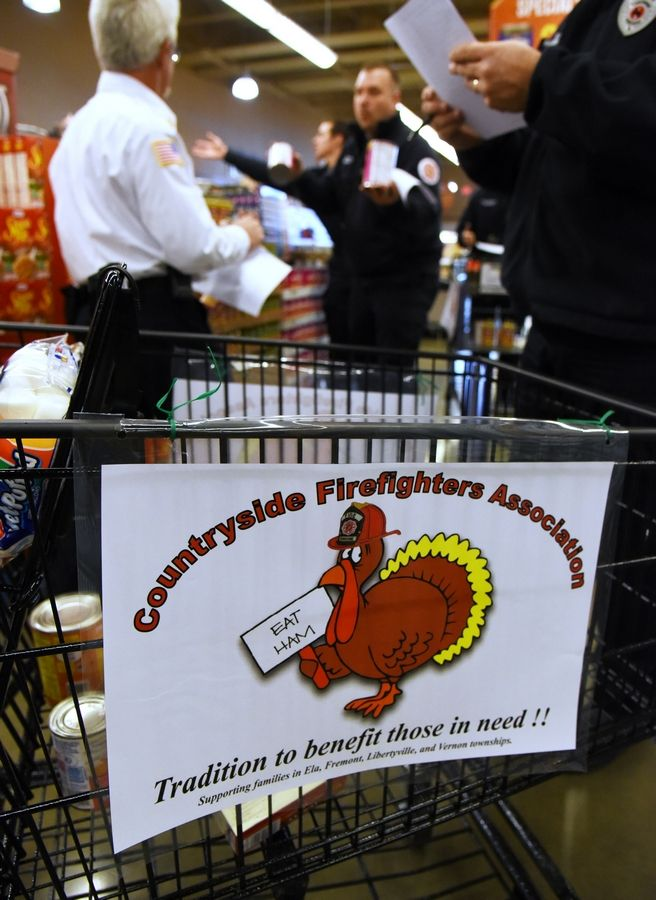 Members of the Countryside Firefighters Association load shopping carts with Thanksgiving dinner items Friday at the Vernon Hills Mariano's. The food will be donated to area families.