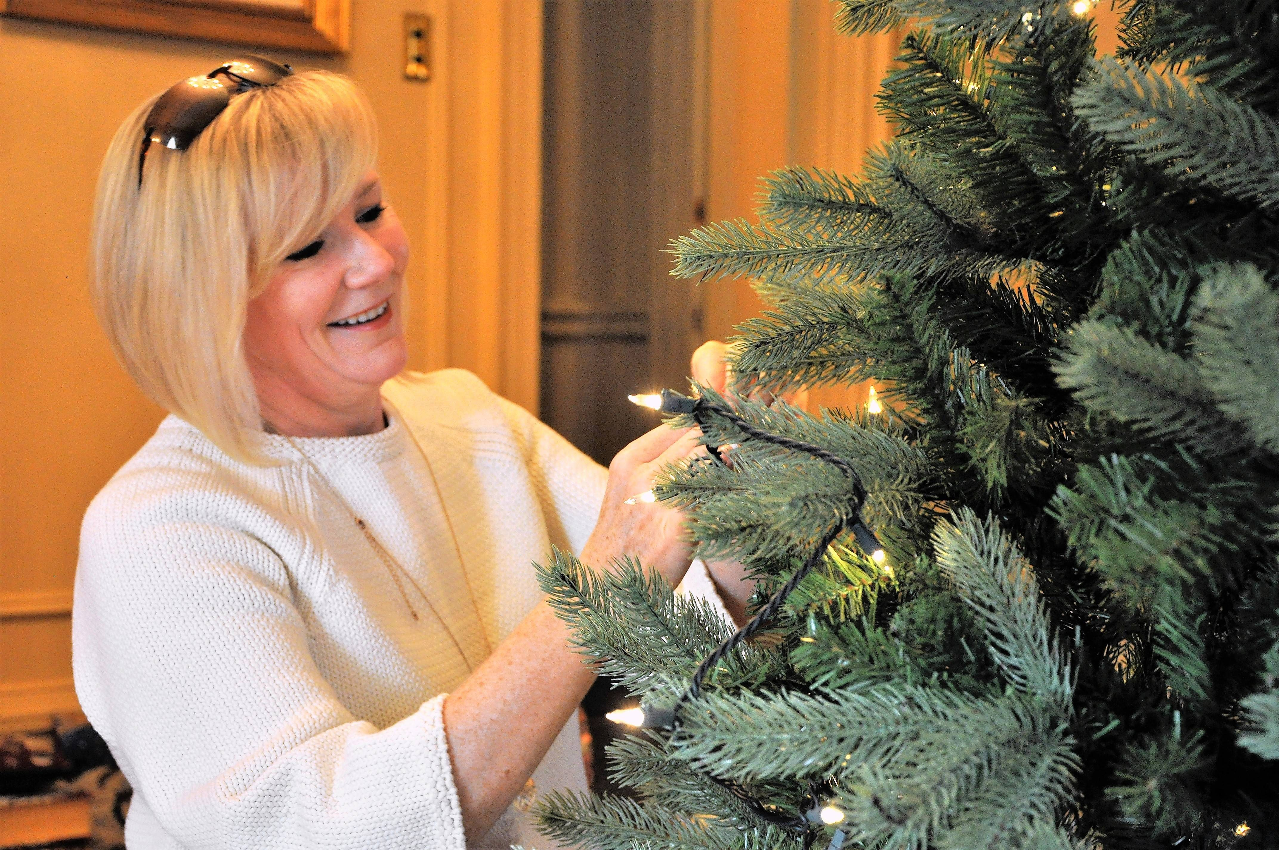 Dawn Violetto of Child's Voice in Wood Dale decorates one of the Community Trees in the McCormick Mansion at Cantigny Park in Wheaton.