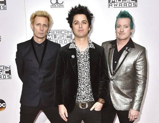 "FILE - In this Nov. 20, 2016 file photo, Mike Dirnt, from left, Billie Joe Armstrong, and Tre Cool, of Green Day, arrive at the American Music Awards in Los Angeles. The band will release their latest, ""Greatest Hits: God's Favorite Band,� on Friday. (Photo by Jordan Strauss/Invision/AP)"
