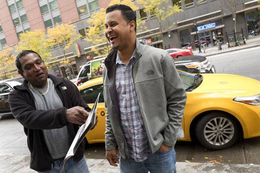 Taxi drivers Terry Samlall, left, and Luis Marte share a laugh about their photos in the NYC Taxi Drivers calendar, Thursday, Nov. 16, 2017 in New York. The NYC Taxi Drivers Calendar has twelve New York City cabbies smirking and smoldering their way through 2018 in a tongue-in-cheek pinup calendar that's raising money for a venerable social-service organization. (AP Photo/Mark Lennihan)