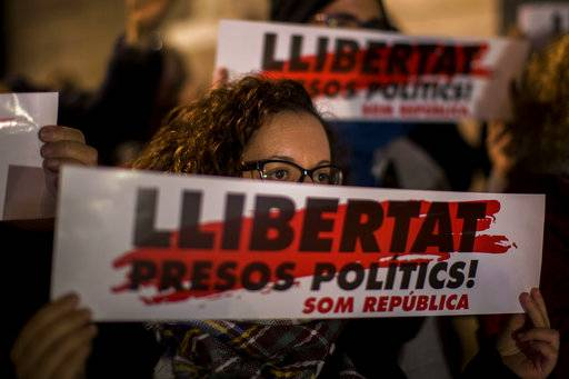 "A woman holds a placard reading in catalan ""freedom for political prisoners"", during a demonstration in front of the Palau Generalitat in Barcelona, Spain, Thursday, Nov. 16, 2017. Demonstrators fill Sant Jaume Square in front of the seat of the Catalan presidency, to mark one month of imprisonment for leaders of the two separatist civil platforms, ANC and Omnium. Eight ex-Catalan cabinet members have also been jailed provisionally. (AP Photo/Emilio Morenatti)"