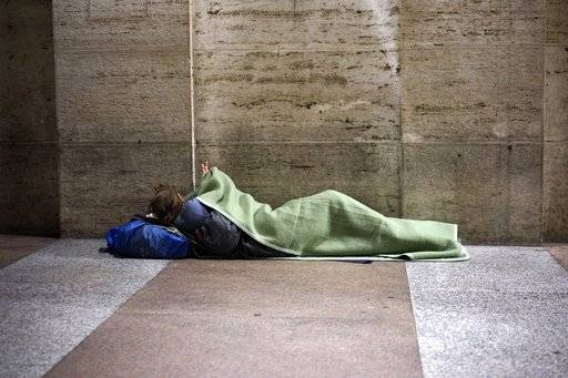 In this photo taken Thursday, Nov. 16, 2017, a homeless man prepares to spend the night under a covered walkway of a building close to the Vatican, in Rome. On the morning of Sunday, Nov. 19, 2017, Pope Francis will host some four thousand poor and vulnerable people in St Peter's Basilica and after a Mass 1.500 of the guests will have lunch with the him in the Paul VI hall in what the pontiff called World Day of the Poor. (AP Photo/Andrew Medichini)