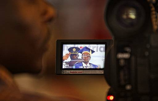 A television cameraman films Zimbabwe's President Robert Mugabe as he speaks at a student graduation ceremony at Zimbabwe Open University on the outskirts of Harare, Zimbabwe Friday, Nov. 17, 2017. Mugabe is making his first public appearance since the military put him under house arrest earlier this week. (AP Photo/Ben Curtis)
