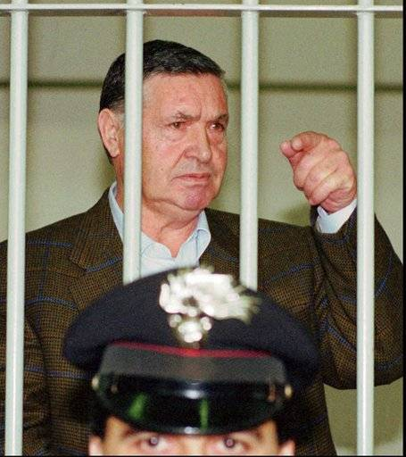 "FILE - In this April 29, 1993 file photo, Mafia ""boss of bosses"" Salvatore ""Toto"" Riina, is seen behind bars, during a trial in Rome. Italian media is reporting that Mafia 'boss of bosses' Salvatore 'Toto' Riina has died while serving multiple life sentences. He was 87. The justice ministry on Thursday, Nov. 16, 2017, had allowed his family a bedside visit at a hospital Parma shortly before his death. He had been placed in a medically induced coma after his health deteriorated following two recent surgeries. (AP Photo/Giulio Broglio, File)"
