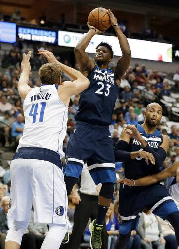 Dallas Mavericks' Dirk Nowitzki (41), of Germany, defends as Minnesota Timberwolves guard Jimmy Butler (23) attempts to shoot in front of Taj Gibson, right, in the first half of an NBA basketball game, Friday, Nov. 17, 2017, in Dallas. (AP Photo/Tony Gutierrez)