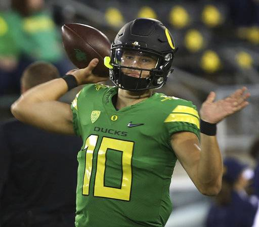FILE - In this Sept. 30, 2017, file photo, Oregon quarterback Justin Herbert warms up before an NCAA college football game against California in Eugene, Ore. Herbert, who fractured his collarbone against California on Sept. 30, has been practicing lately and some say he appears ready to come back in their game against Arizona, Saturday, Nov. 18, 2017, in Eugene. (AP Photo/Chris Pietsch, File)