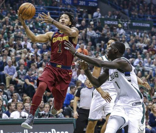FILE - In this Oct, 20, 2017, file photo, Cleveland Cavaliers' Derrick Rose, left, drives to the basket as Milwaukee Bucks' Thon Maker, right, defends during the first half of an NBA basketball game in Milwaukee. Rose will miss at least the next two weeks with a nagging left ankle injury. He injured the ankle Oct. 20 at Milwaukee and has missed Cleveland's past four games. He underwent medical tests and was recommended to rest. (AP Photo/Tom Lynn, File)