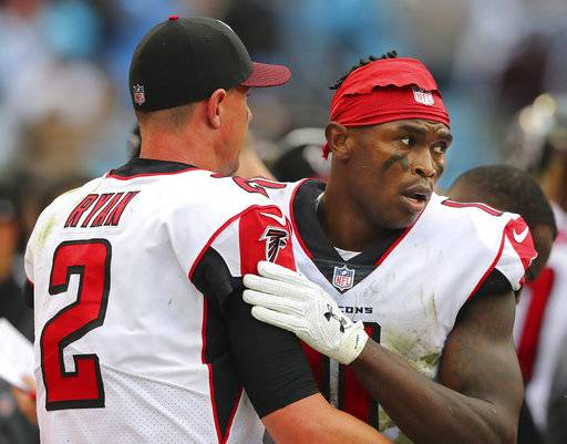 Falcons wide receiver Julio Jones gives quarterback Matt Ryan a hug on the sidelines after he dropped a certain touchdown pass in the end zone during the fourth quarter against the Panthers in a NFL football game on Sunday, Nov. 5, 2017, in Charlotte. The Panthers held on to beat the Falcons 20-17. (Curtis Compton/Atlanta Journal-Constitution via AP)