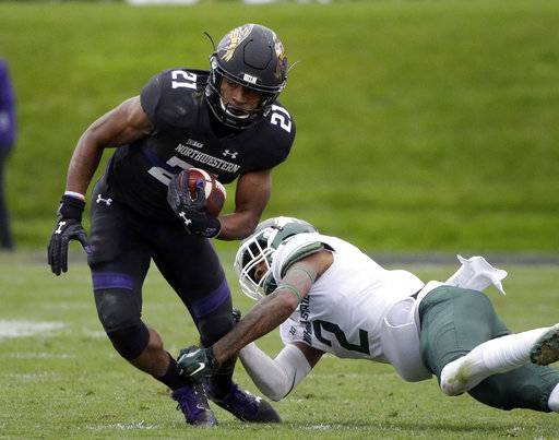 FILE - In this Oct. 28, 2017, file photo, Northwestern running back Justin Jackson, left, is tackled by Michigan State cornerback Justin Layne during the first half of an NCAA college football game in Evanston, Ill. Jackson, Northwestern's career rushing leader, needs 156 yards to join Wisconsin great Ron Dayne as the only Big Ten players with four 1,000-yard seasons.