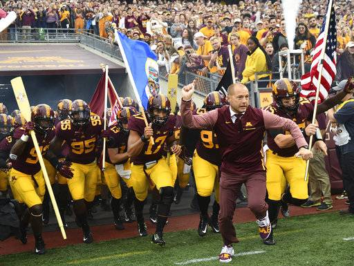 FILE - In this Oct. 21, 2017, file photo, Minnesota coach P.J. Fleck leads his team onto the field for an NCAA college football game against Illinois in Minneapolis. Minnesota faces Northwestern this week. Fleck recalls the advice about running a program he got from Northwestern's Pat Fitzgerald over lunch many years ago. It still resonates.