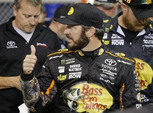 Martin Truex Jr. walks on pit road before qualifying for Sunday's NASCAR Cup Series auto race at Homestead-Miami Speedway in Homestead, Fla., Friday, Nov. 17, 2017. (AP Photo/Terry Renna)