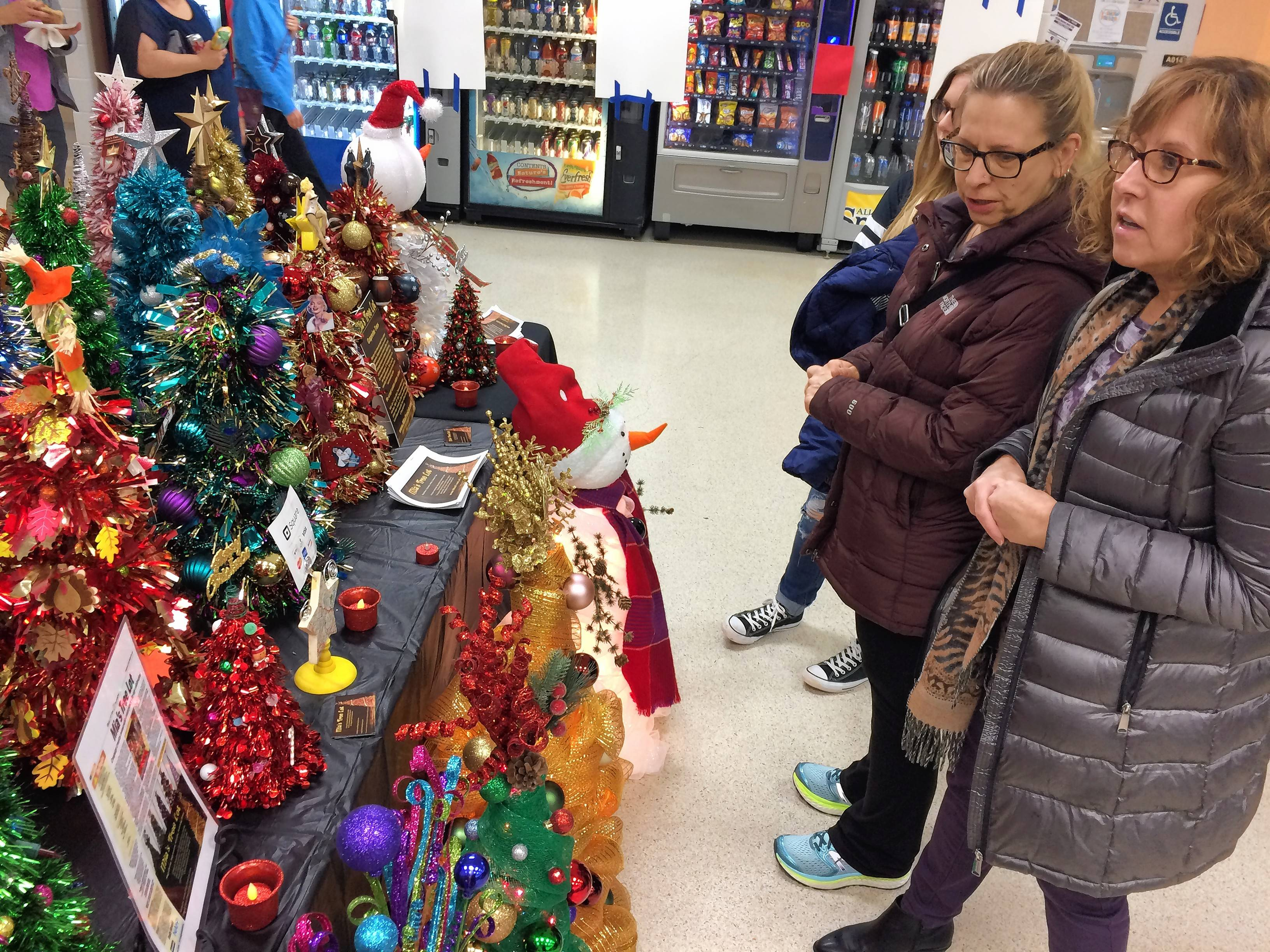 Sue Labbe, left, and Beth Avandado check out a display of tabletop artificial Christmas trees from an Oswego business called Mia's Tree Lot on Saturday at Rolling Meadows High School. The school's athletic booster club held a craft fair.