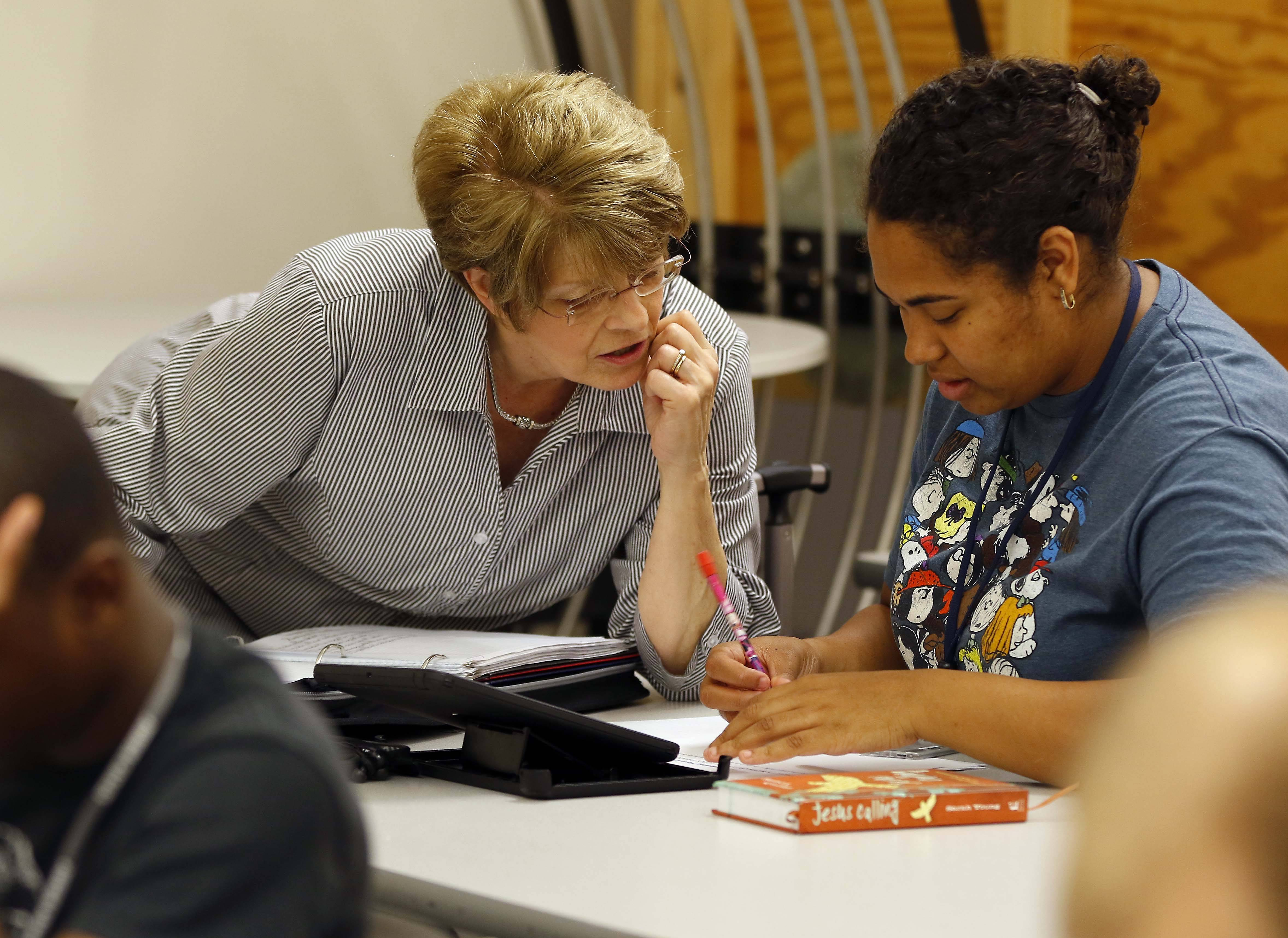Kathy Lambert, left, works with Serena Williams of Carpentersville, one of 12 students in Judson University's new RISE two-year certificate program for students with intellectual disabilities. RISE stands for Road to Independent Living, Spiritual Formation and Employment.