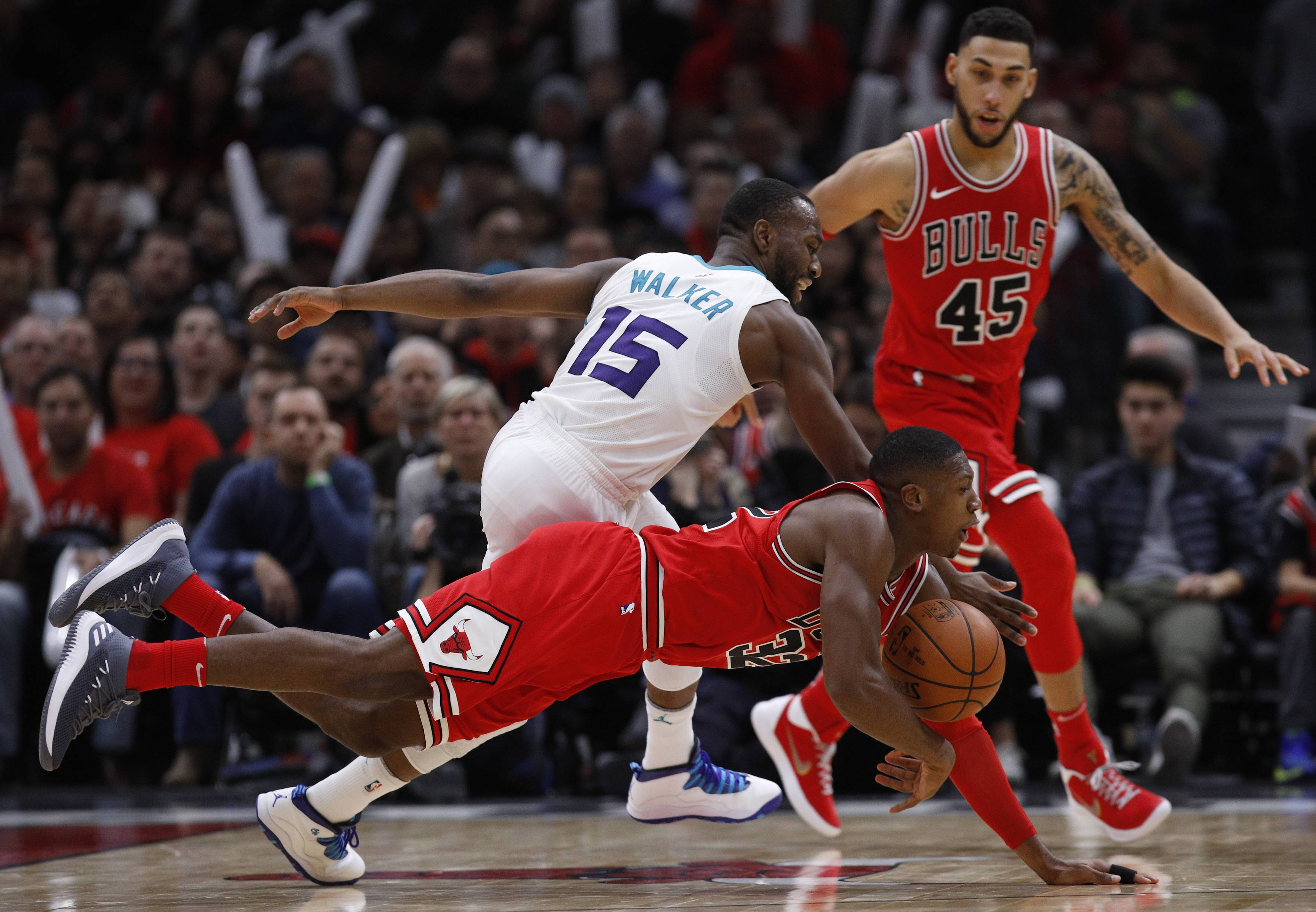 Chicago Bulls' Kris Dunn dives for the ball against Charlotte Hornets' Kemba Walker (15) as Bulls' Denzel Valentine (45) looks on during the second half of an NBA basketball game Friday, Nov. 17, 2017, in Chicago. (AP Photo/Jim Young)