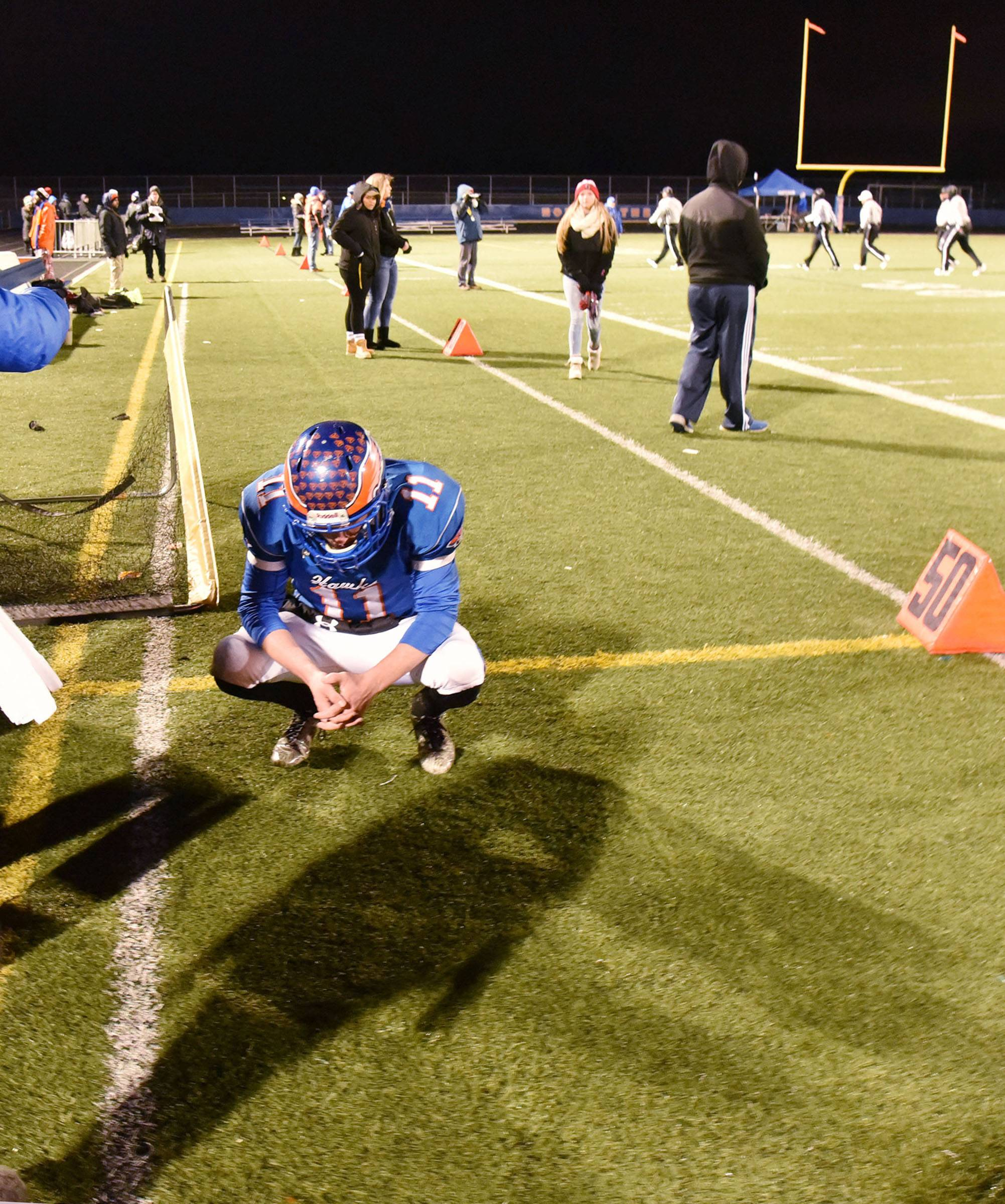 Hoffman Estates' Austin Coalson take a moment to himself after the Hawks loss to Prairie Ridge Saturday in the Class 6A semifinal football game in Hoffman Estates.