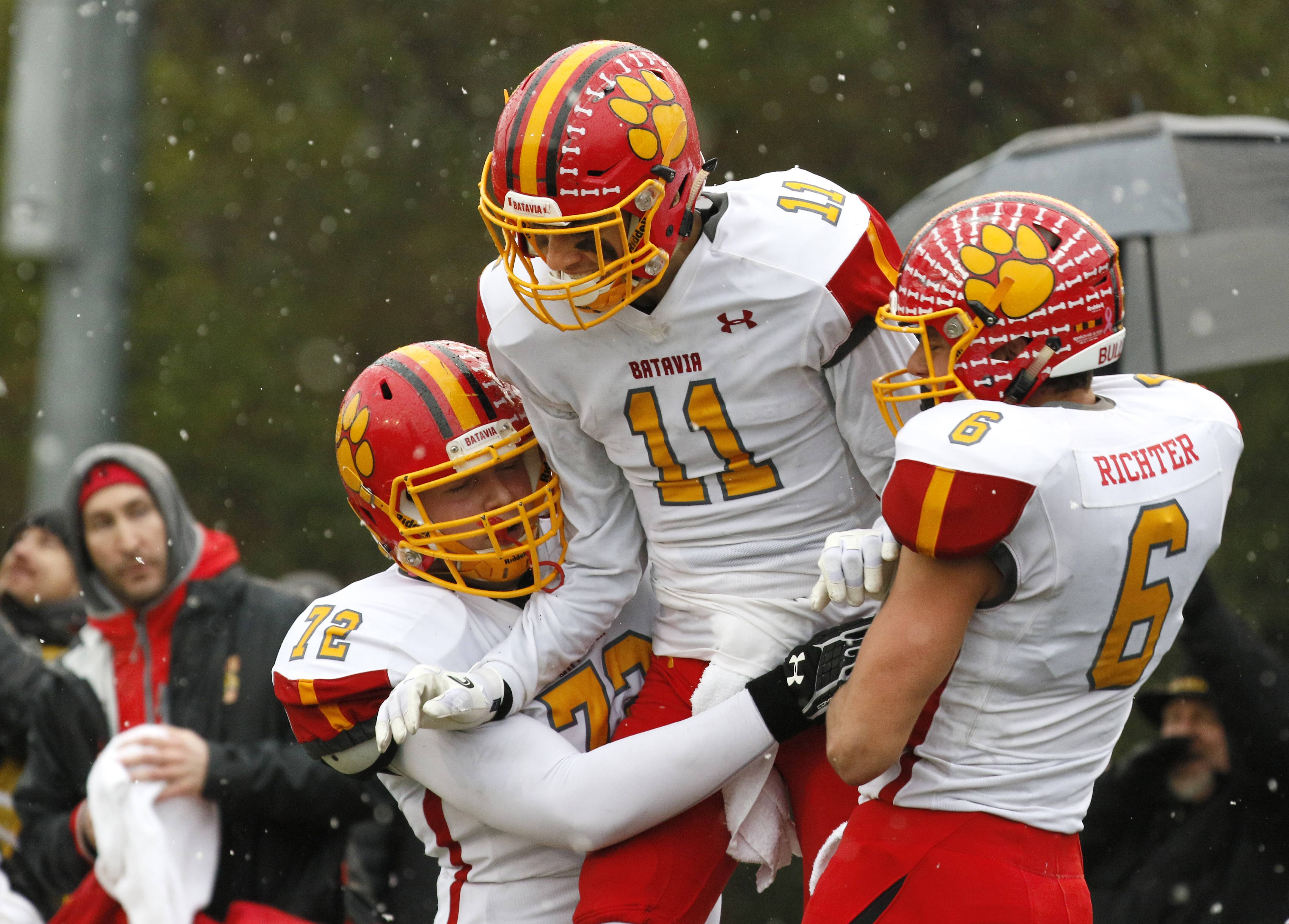Batavia's Eric Peterson (11) is hoisted into the air by Evan Holden (72) and Collin Richter (6) after scoring his second touchdown during a 23-13 win over Benet Academy in the Class 7A football semifinal game in Lisle.