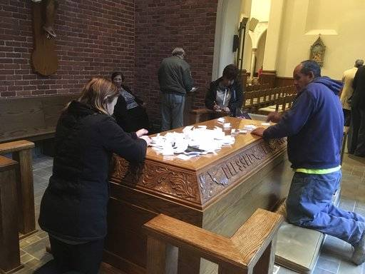 FILE- In this Nov. 15, 2017 photo, people pray at the tomb of Father Solanus Casey in Detroit. The Detroit priest, who is credited with helping cure a woman with a skin disease, is being beatified by the Roman Catholic Church, a major step toward sainthood, Saturday, Nov. 18 in Detroit. More than 60,000 people are expected Saturday at a Mass at Ford Field. (AP Photo/Ed White)