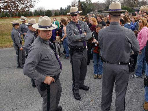 FILE--This photo from Tuesday, Nov. 10, 2009 shows New York State Police waiting with families for students to be released after a lockdown at Stissing Mountain Middle School and High School in Pine Plains, N.Y. The president of the National Association of School Resource Officers says schools regularly practice safety plans and have gotten good at taking action anytime they hear about a potential threat in or outside the building. (AP Photo/Mike Groll, File)