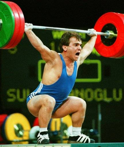 "FILE- In this July 22, 1996 file photo, Naim Suleymanoglu, of Turkey, lifts 147.5kg, at the Summer Olympics in Atlanta. Turkey's official news agency said Saturday, Nov. 18, 2017, Suleymanoglu, the Turkish weightlifter who was known as ""Pocket Hercules"" and who won three straight Olympic gold medals for Turkey between 1988 and 1996, has died. Suleymanoglu was considered one of the sport's greatest athletes and earned his nickname for his strength and diminutive size. He was 50. (AP Photo/Michael Probst, File)"