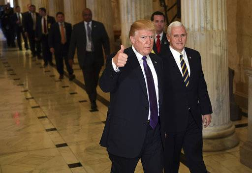 President Donald Trump gives a thumbs up as he walks with Vice President Mike Pence as he departs Capitol Hill in Washington, Thursday, Nov. 16, 2017. Trump urged House Republicans Thursday to approve a near $1.5 trillion tax overhaul as the party prepared to drive the measure through the House. Across the Capitol, Democrats pointed to new numbers showing the Senate version of the plan would boost taxes on lower and middle-income Americans. (AP Photo/Susan Walsh)