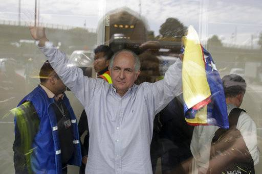 Holding a national Venezuelan flag, ousted Caracas Mayor Antonio Ledezma waves from inside El Dorado international airport, as he prepares for departure, in Bogota, Colombia, Friday, Nov. 17, 2017. Ledezma, one of Venezuela's most prominent opposition leaders, said he plans to take his fight against Venezuela's socialist government to Europe after he escaped house arrest in Caracas, and fled to Colombia on Friday. (AP Photo/Ricardo Mazalan)