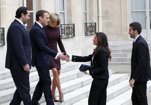 French President Emmanuel Macron, second left, and his wife Brigitte, centre left, greet Lebanon's Prime Minister Saad Hariri, left, his wife Lara, center center and their son Hussam, right, upon their arrival at the Elysee Palace in Paris, Saturday, Nov. 18, 2017. Hariri arrived in France on Saturday from Saudi Arabia and may be back in Beirut next week, seeking to dispel fears that he had been held against his will and forced to resign by Saudi authorities.(AP Photo/Christophe Ena)