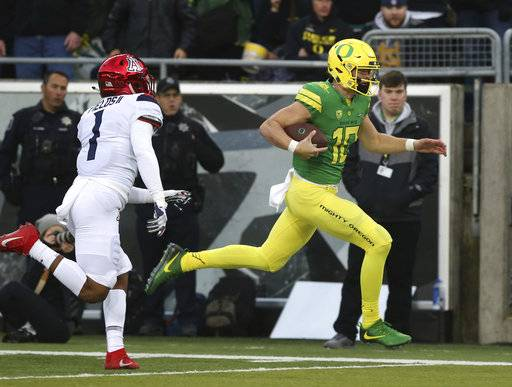 Oregon's quarterback Justin Herbert, right, rushes for the end zone ahead of Arizona's Tony Fields II for a touchdown during the first quarter of an NCAA college football game, Saturday, Nov. 18, 2017, in Eugene, Ore. (AP Photo/Chris Pietsch)