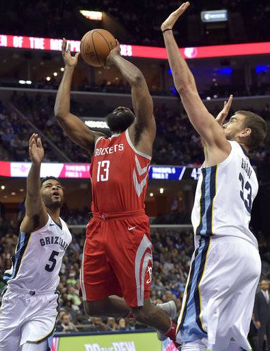 Houston Rockets guard James Harden (13) shoots between Memphis Grizzlies center Marc Gasol (33) and guard Andrew Harrison (5) during the first half of an NBA basketball game Saturday, Nov. 18, 2017, in Memphis, Tenn. (AP Photo/Brandon Dill)